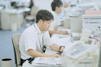 男性社員がパソコンでメールチェックをしている写真