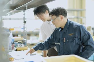 男性社員2人が資料のチェックをしている写真