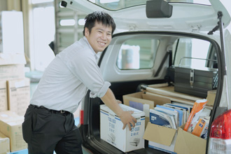 笑顔の男性社員が車に資料を詰め込んでいる写真