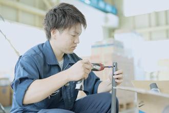 若い男性社員が機材を組み立てている写真