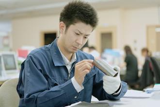 若い男性が部品チェックを行っている写真