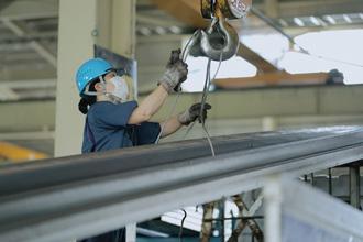 男性が機械のフックに鉄骨を固定している写真