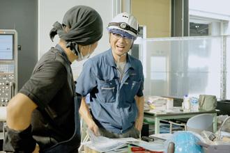 男性社員が笑顔で会話している写真