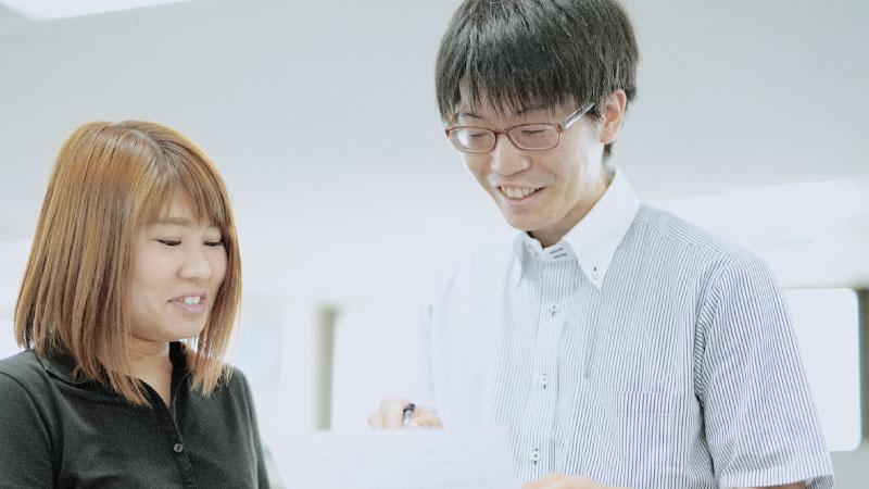 笑顔で同僚と話している画像